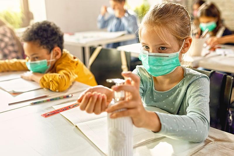 Girl in school using hand sanitizer