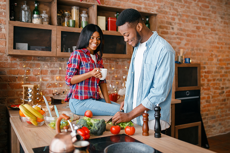 Couple in their kitchen making dinner. Cooking can cause poor IAQ indoor air quality.