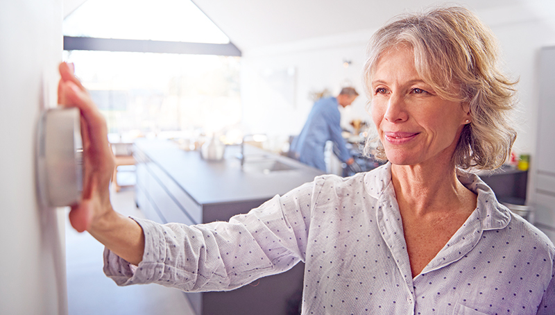 Woman changing temperature in her home with wall thermostat